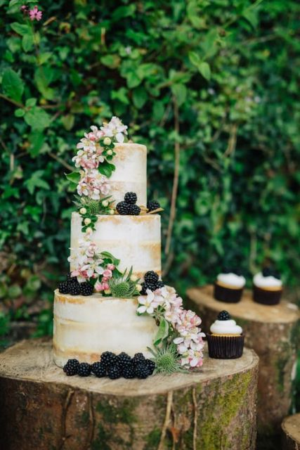 Wedding cake and cupcakes decorated with blackberries