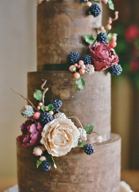 Wedding cake with flowers, ripe and unripe blackberries