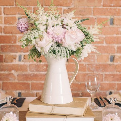 Wedding centerpiece with white jug, roses, peonies and greenery