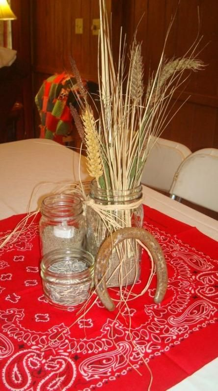 a rustic centerpiece of a horseshoe, wheat and herbs, some dried herbs in jars that give an aroma
