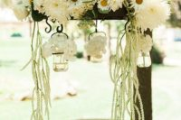 a rustic decoration of lush white blooms and greenery hanging over the reception – for a bridal shower or a wedding