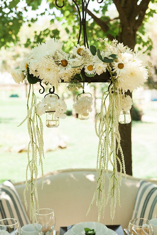 a rustic decoration of lush white blooms and greenery hanging over the reception   for a bridal shower or a wedding