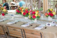 a rustic tablescape covered with burlap, a colorful printed runner, bright blooms in neutral vases and simple napkins