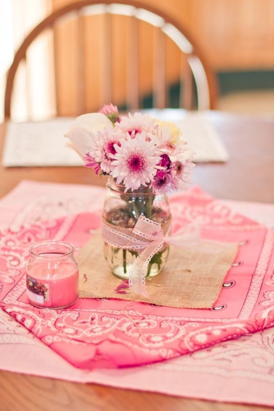 a simple bridal shower centerpiece of a jar with pink ribbons and pink blooms and a pink candle plus pink linens