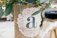 a tin can wrapped with burlap and with a doily, greenery and flowers for a centerpiece