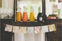 a vintage and rustic drink bar with a colorful floral bunting, juices and glasses for a chic look