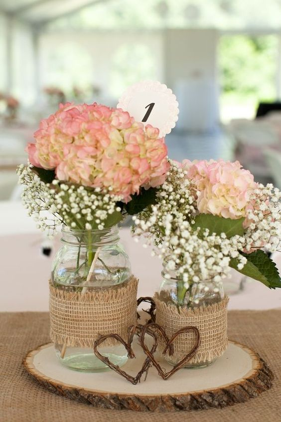 jars with hydrangeas and baby's breath wrapped with burlap and placed on a wooden slice