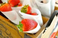 paper cones with fresh strawberries is a cool dessert or favor idea for a cowgirl bridal  shower