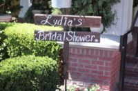style your sign with a bucket with bright blooms over it to embrace the style of your shower