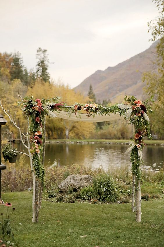 moody wooden arch with dark florals and greenery