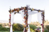 18 rustic twig arch with bold florals and white fabric