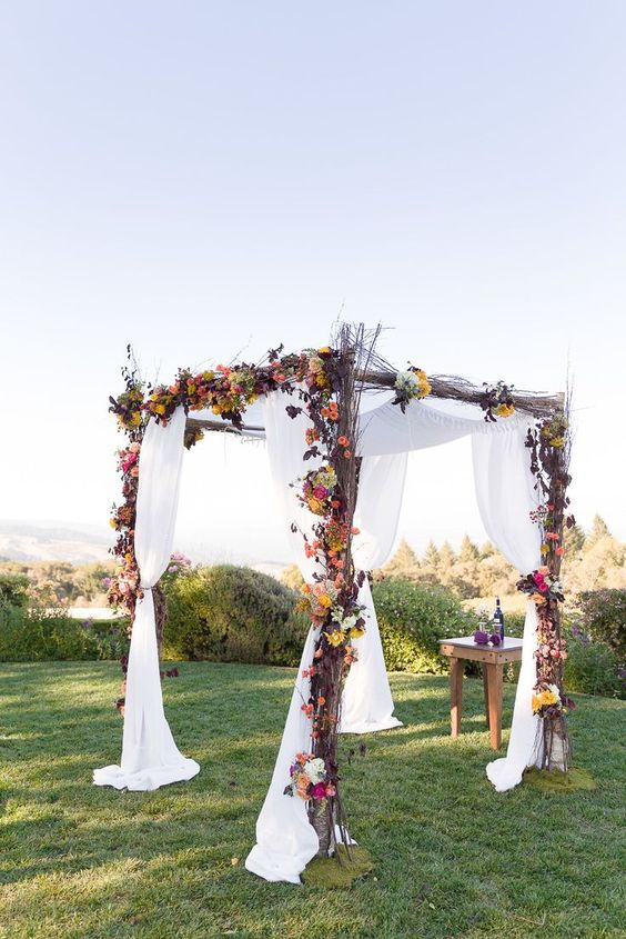 rustic twig arch with bold florals and white fabric
