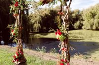 21 rustic living arch with bold red flowers