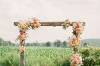22 rustic wedding arch with some orange and cream flowers