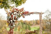 25 wooden arch with a corner decorated with fall leaves and white flowers