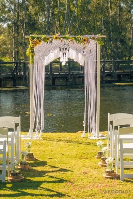 Macrame knotted wedding backdrop with sunflowers