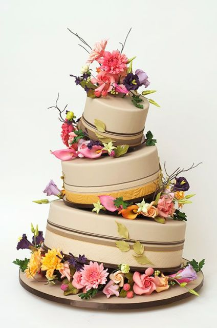 Topsy turvy wedding cake with flowers between tiers