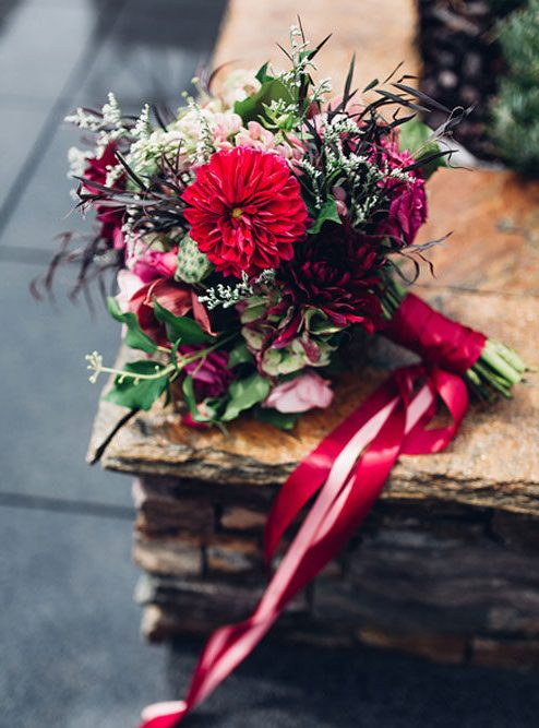 the bouquet of the first bride was done in red to contrast with the dress