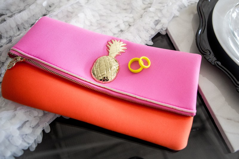 Neon yellow rings and a red and pink clutch