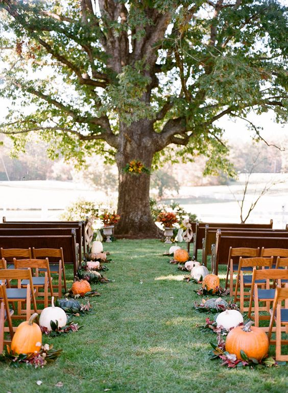 fall wedding aisle decorated with pumpkins