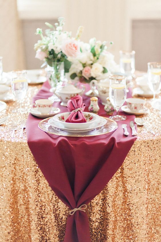 gold sequin tablecloth and a burgundy table runner over it