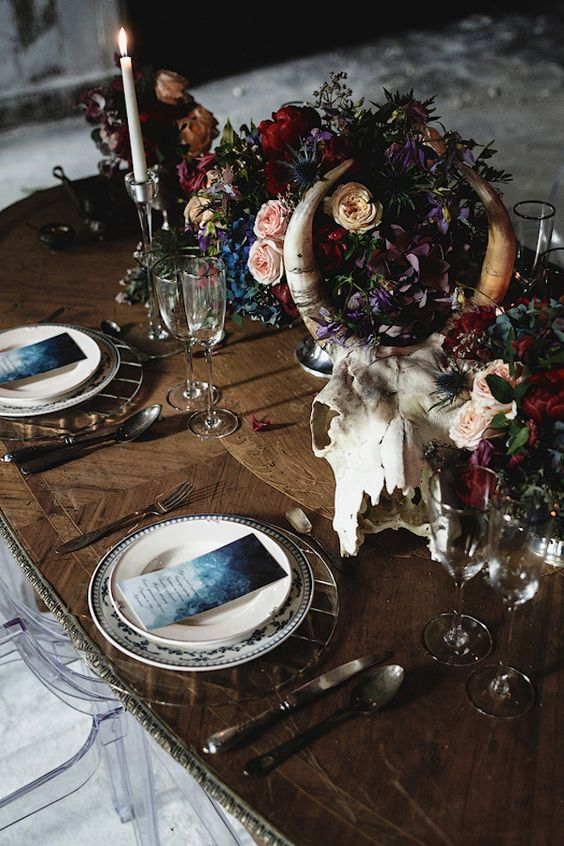 moody boho tablescape with a skull and flowers centerpiece
