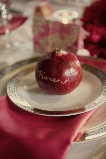 pomegranate with a gold name as an escort card
