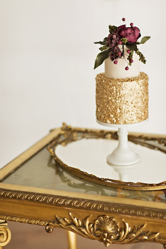 gold and white wedding cake with marsala flowers decor