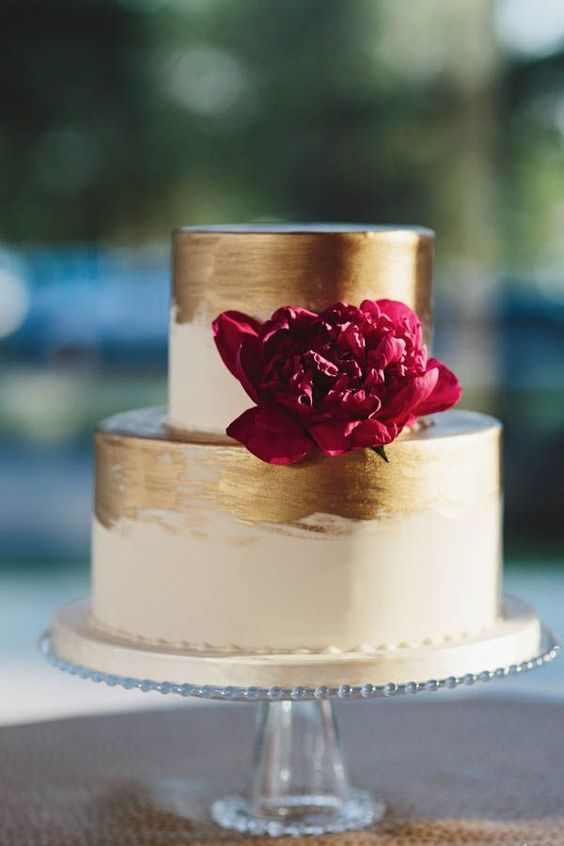 metallic gold wedding cake with a burgundy flower