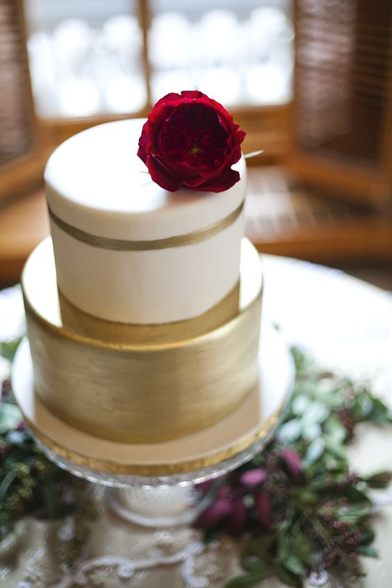two-tiered wedding cake with a flower on top
