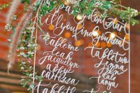 Lucite seating plan decorated by greenery