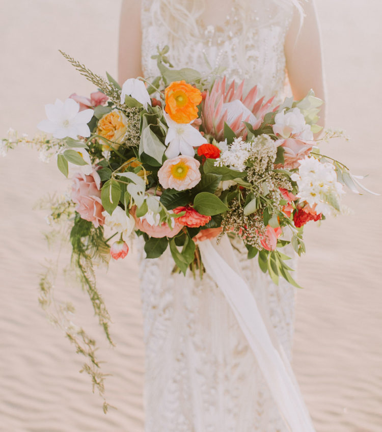 her colorful bouquet contrasted with light sands