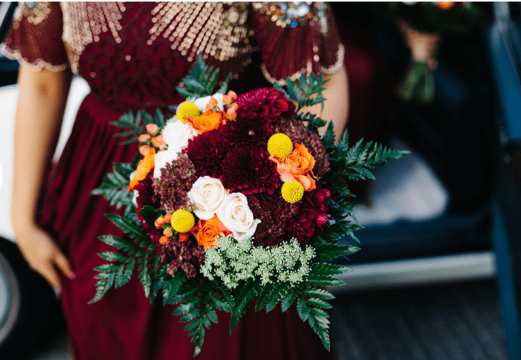 Rich fall colors were incorporated into the wedding, for example, burgundy, yellow, orange and emerald in this halloween-inspired wedding bouquet