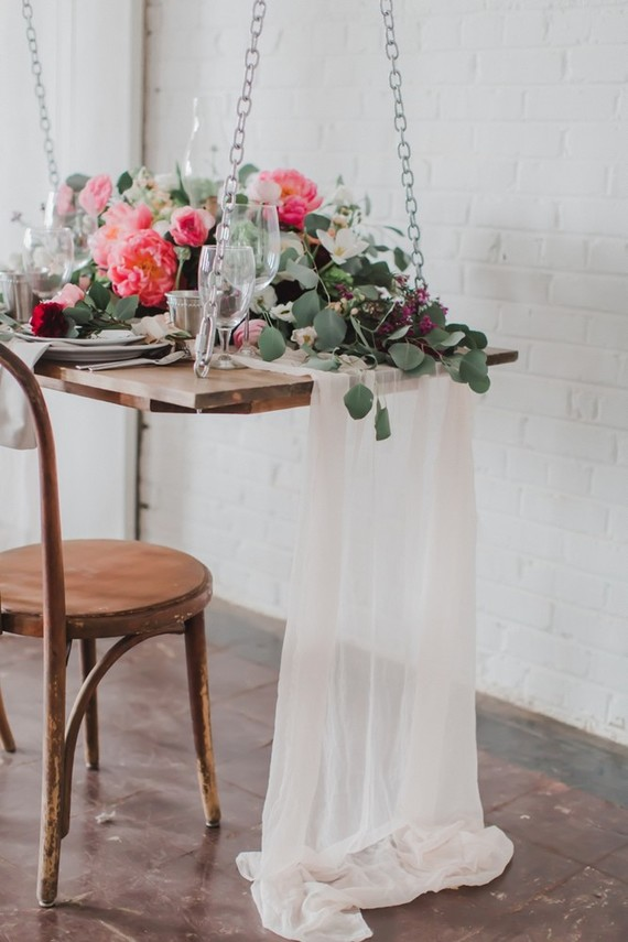 The delicate fabric table runner and florals soften the industrial space