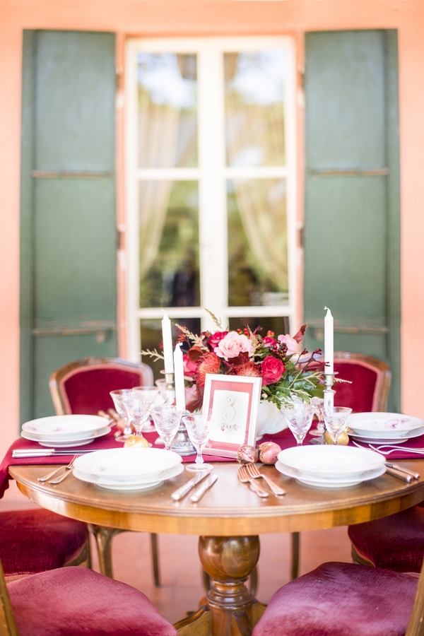 The wedding table setting is also bold red and crimson velvet chairs highlight the look