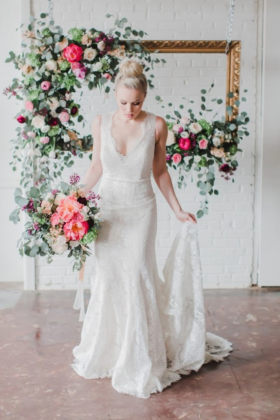 The bride was wearing an elegant ivory lace wedding dress with a plunging neckline and a train