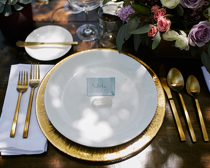 The table setting features gold tableware, chargers, various flowers and crystals