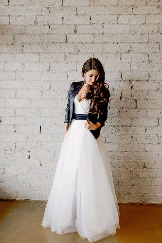 tulle wedding dress with a black sash and a black jacket