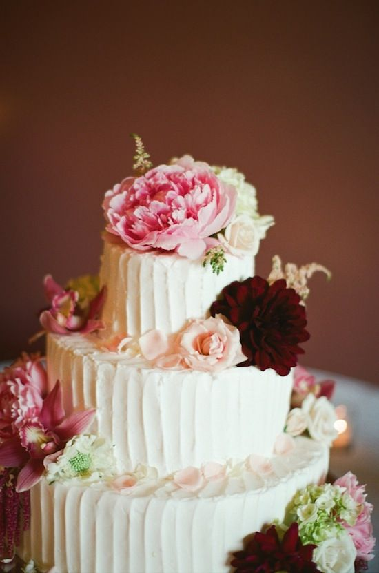 cake topped with beautiful pink peonies, roses, and burgundy dahlias