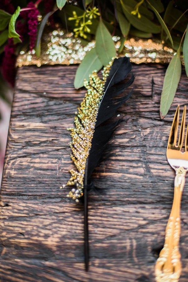 gold-painted feathers are a unique table accessory for a wicked wedding style