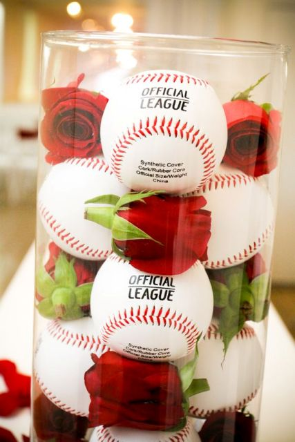 Baseballs and red roses in glass vase