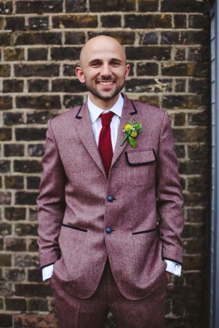 Pink tweed jacket with red tie and green and yellow boutonniere