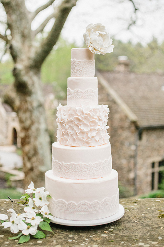 Fire-tiered lace wedding cake with a floral tier keeps the wedding theme perfectly