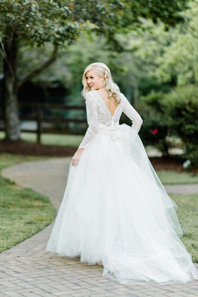 The bride was wearing a ball gown dress with a tulle skirt and a lace top