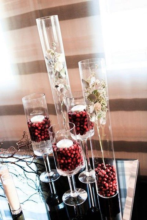 tall vases filled with cranberries and topped with floating candles