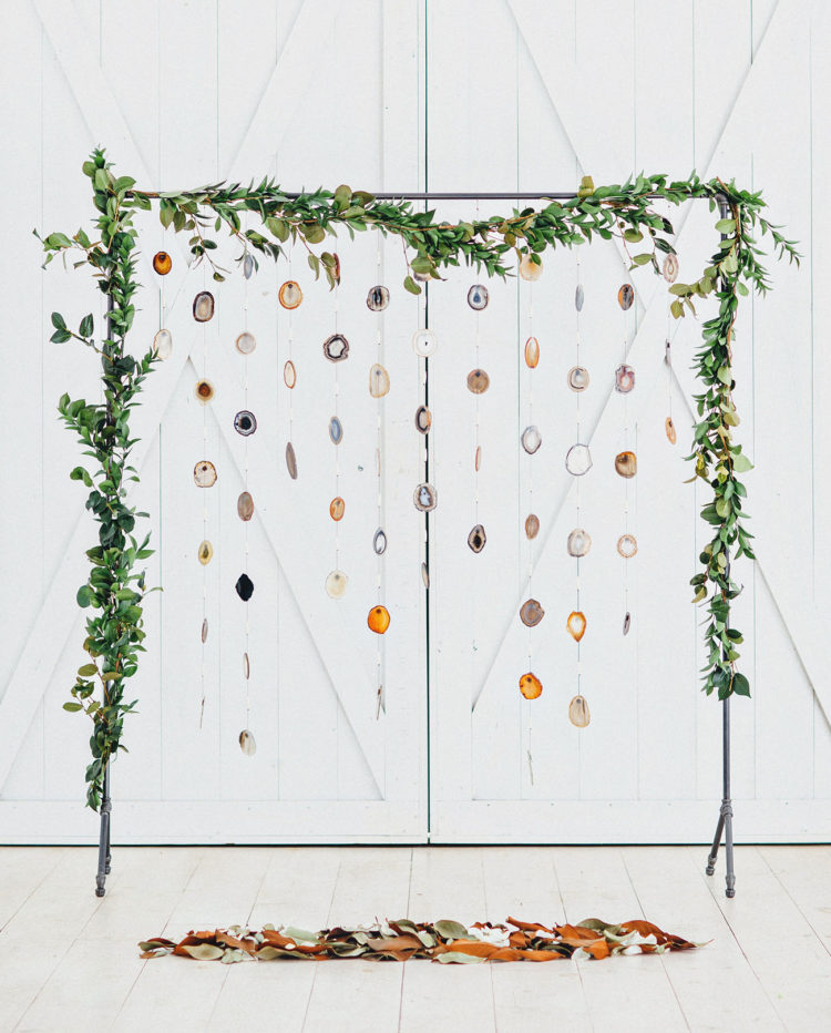 A custom-made wedding backdrop was made of agate slices and topped with a camellia garland