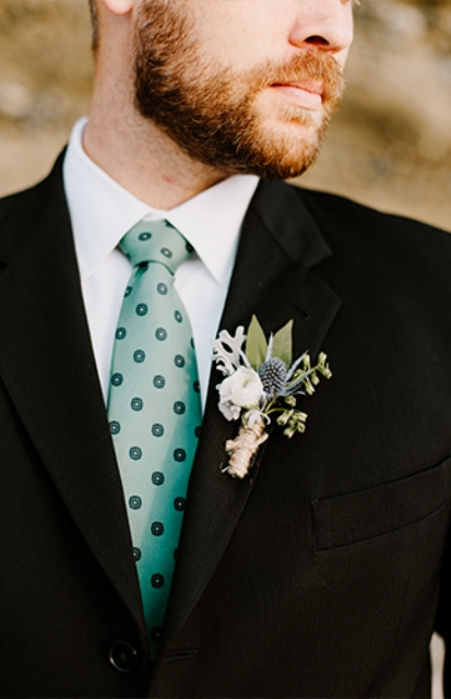The groom wore a sea glass colored tie and boutonniere