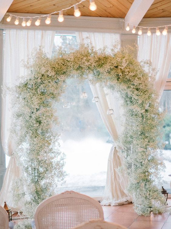 baby's breath wedding arch with hanging candle holders will make your ceremony heavenly and elegant