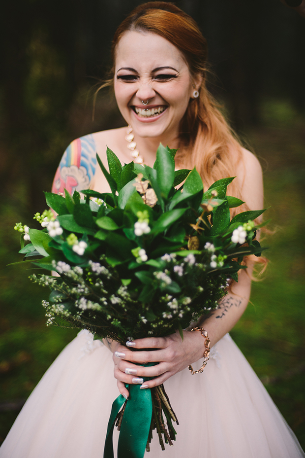 The bridal bouquet was made of greenery and white flowers and decorated with emerald ribbon