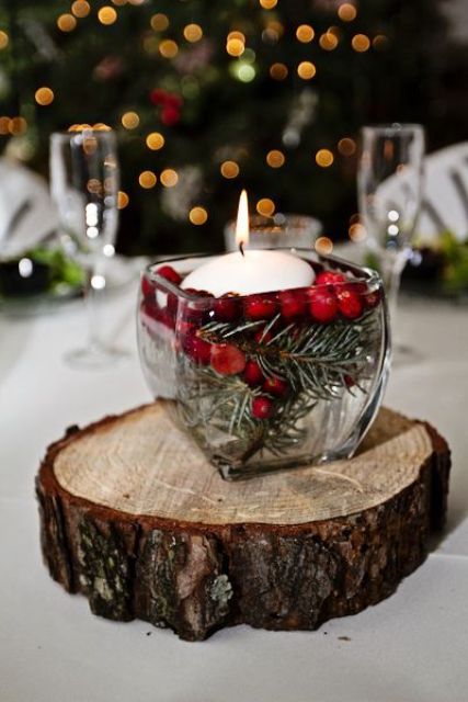 winter wedidng centerpiece with a floating candle, fir branches and cranberries